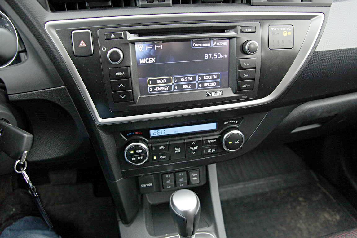 Дешевый пластик торпедо Toyota Auris живо перекликается с унылой синей подсветкой, монохромными часами и индикатором климат-контроля, но не с передовой внешностью хэтчбека